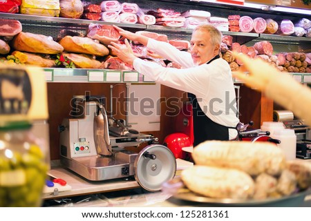 Shopkeeper serving a customer in a grocery store - stock photo
