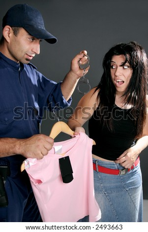 Shoplifting is a crime.  A security guard dangles handcuffs at a shoplifter.  Retailers lose $25 million a day to shoplifting. - stock photo