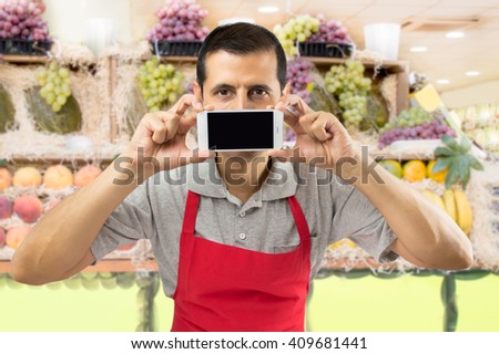 shopman holding a mobile phone against her mouth at the greengrocery   - stock photo