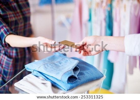 Shopper hand giving plastic card to shop assistant - stock photo