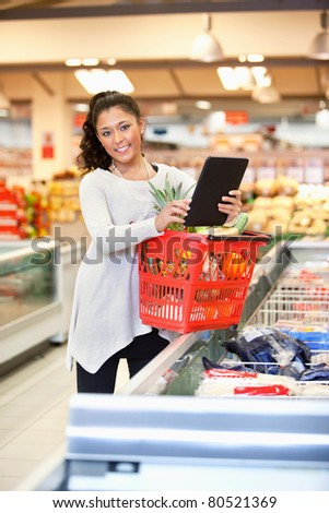 Shopper with basket holding digital tablet and looking at camera