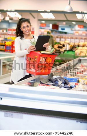 Shopper with basket holding shopping list on digital tablet and looking at camera - stock photo