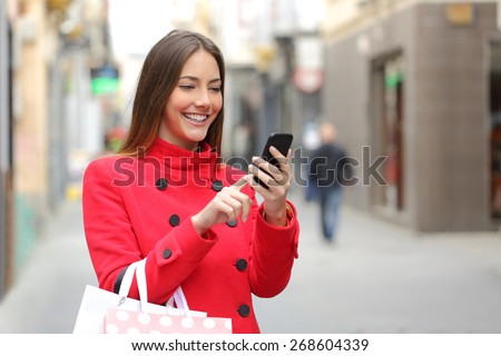 Shopper woman buying online on the smart phone in the street - stock photo