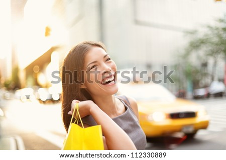 Shopper woman on Manhattan, New York City shopping having fun laughing outside in streets of New York. Fresh blissful mixed race Asian / Caucasian girl holding shopping bag. - stock photo