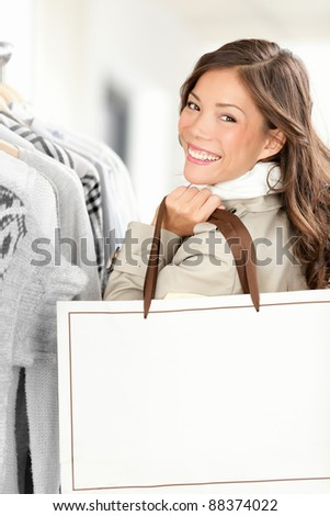 Shopper woman showing shopping bag with copy space. Smiling Caucasian / Chinese Asian female model buying clothes in clothing store. - stock photo