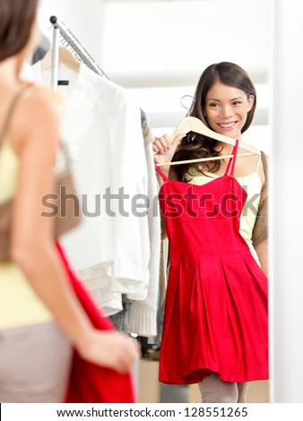 Shopper woman trying clothing dress while shopping in clothes store during sale. Beautiful young multicultural Asian / Caucasian female model smiling happy and joyful. - stock photo