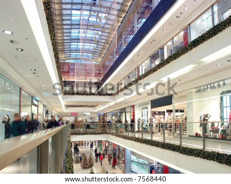 Shoppers doing christmas shopping in big shopping center decorated with christmas ornaments and lights - stock photo