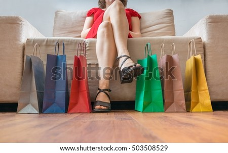 Shopping and consumerism concept. Legs of young woman sitting on sofa and many colorful shopping bags.