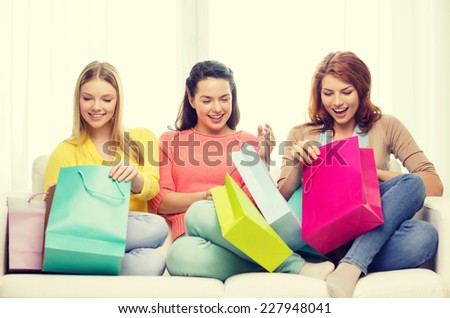 shopping and lifestyle concept - three smiling teenage girls with many shopping bags at home - stock photo