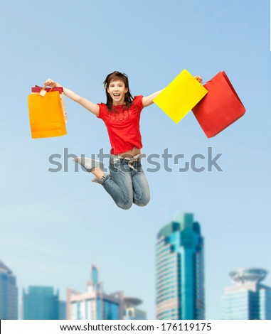 shopping and movement concept - happy girl with shopping bags .