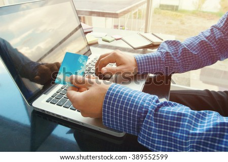 Shopping and payment online. Male hands close up hold credit card typing numbers on computer laptop keyboard sitting at the table at home or office. Online banking. - stock photo