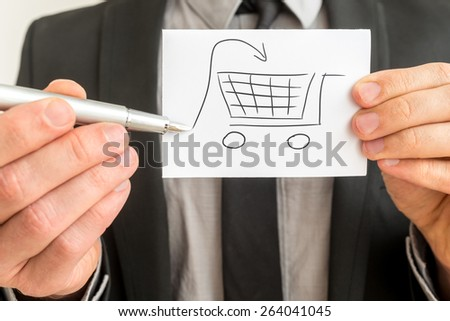 Shopping and purchases concept with a businessman holding up a hand-drawn sketch of a shopping cart with an input arrow in his hand with a pen, close up view of the card. - stock photo