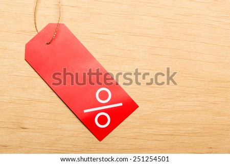 Shopping and sale concept. Red price label with percent sign on wooden surface background. Copyspace - stock photo