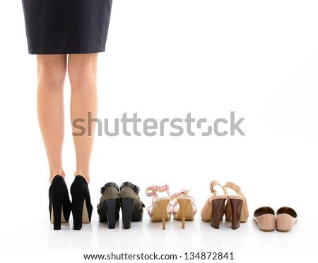 Shopping and sale. Female legs with shoes assortment, young woman put shoes on in shop and makes her choice, back view. Over white background - stock photo