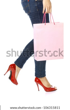 Shopping bag, jeans, and high heels closeup with copy space on shopping bag. Shopping woman profile close up isolated on white background,