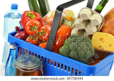Shopping basket and groceries on white background - stock photo