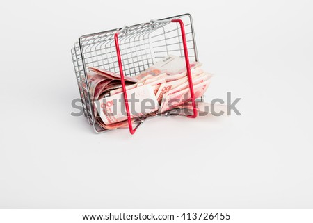 Shopping basket or cart full of Yuan - currency. Symbolic example of spending money in shops, or advantageous purchase in the shopping center. Yuan notes from China's currency. Chinese banknotes