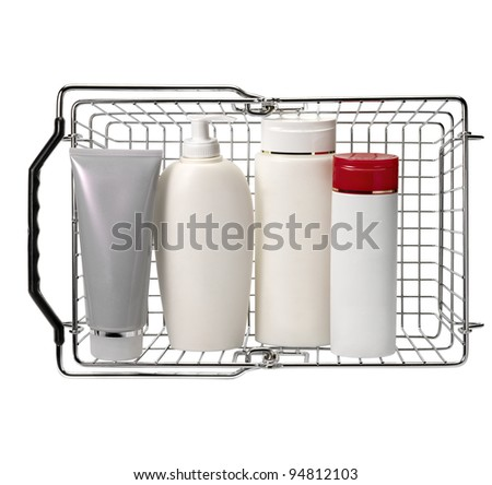Shopping basket with cosmetics containers against white background - stock photo