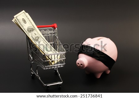Shopping basket with stack of money american hundred dollar bills inside and pink piggy bank with black blindfold standing on black background - horizontal - stock photo