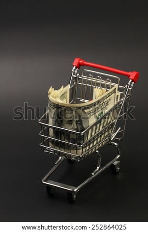 Shopping basket with stack of money american hundred dollar bills inside standing on black background - vertical - stock photo