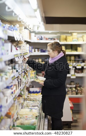 Shopping - Beautiful woman looking different items in store - stock photo