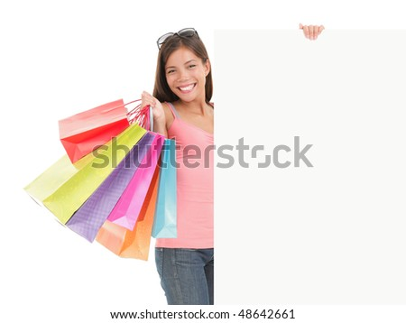 Shopping billboard sign. Shopping woman showing commercial sign. Picture of a beautiful young mixed race woman holding a blank billboard sign while standing with shopping bags. Isolated on white. - stock photo