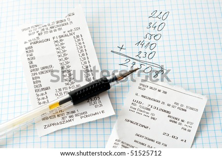 Shopping bills and calculations on a white paper