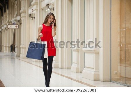 Shopping, calling by phone. Beautiful young brunette woman in red dress, holding shopping bags walking in the shop - stock photo