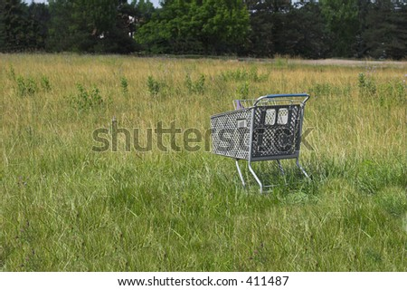 Shopping cart abandoned in an empty field. - stock photo