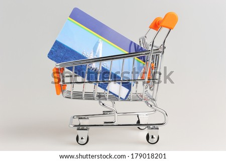 Shopping cart and credit card within on gray background