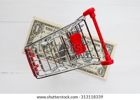 Shopping cart and dollar on the white wooden surface