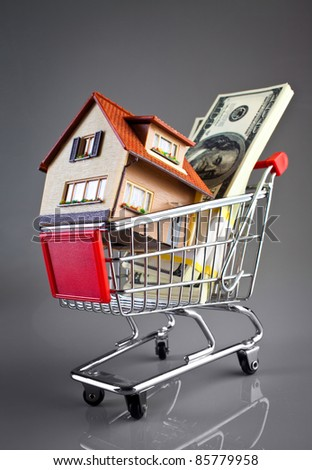 shopping cart and house on a grey background - stock photo