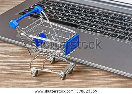 Shopping cart and laptop on table - stock photo