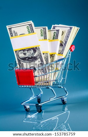 shopping cart and money on a blue background