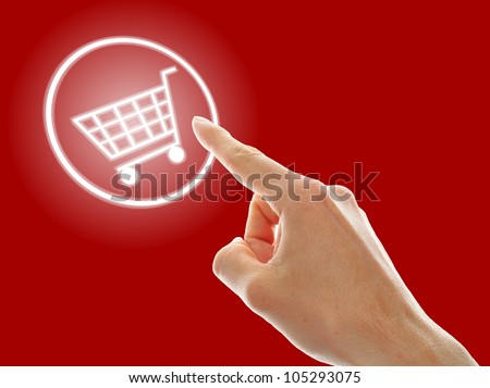 shopping cart button presses by a male hand on red background - stock photo
