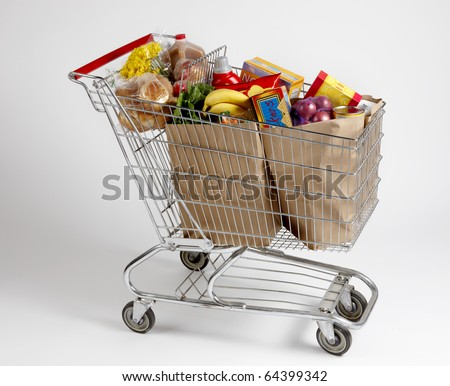 Shopping cart filled with bagged groceries shot on white with soft shadows - stock photo