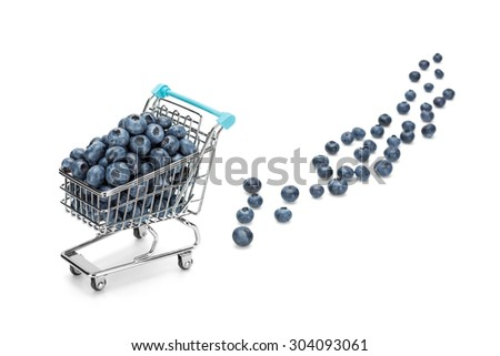 Shopping cart filled with blueberries on pure white background with some blueberries fallen out. Healthy shopping and eating concept. - stock photo