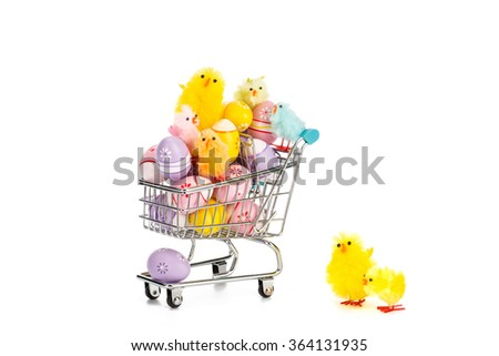 Shopping cart filled with colored easter eggs and happy colored easter chickens on white background.