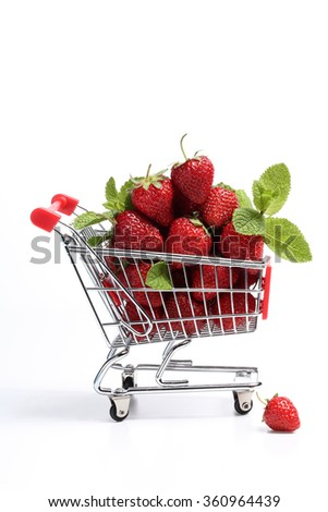 Shopping cart filled with fresh strawberries isolated over white. Healthy shopping and eating concept. Close up. - stock photo
