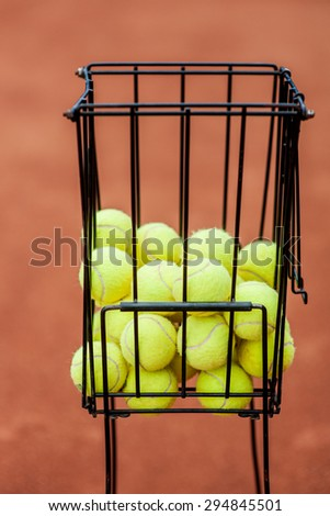 Shopping cart filled with tennis balls on a tennis court background of red color - stock photo