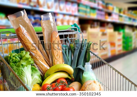 Shopping cart full of food in the supermarket aisle. High internal view. Horizontal composition - stock photo