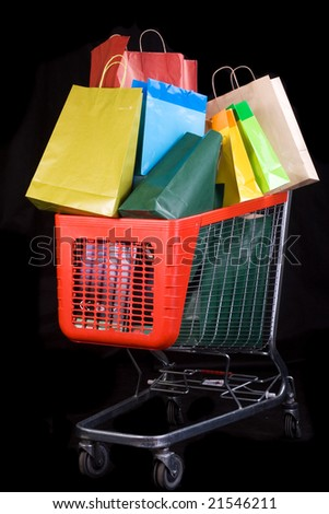 Shopping cart full of gifts on black background - stock photo