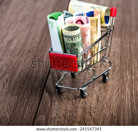 Shopping cart full of money (dollar, euro). Multi currency basket concept - stock photo