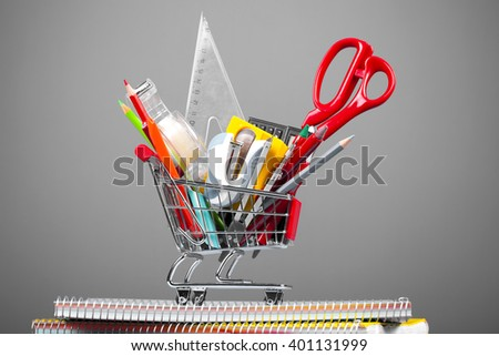 Shopping cart full of school tools on grey background - stock photo