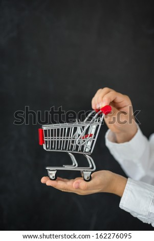 Shopping cart in hands against blackboard blank
