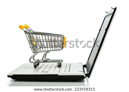shopping cart is on the keyboard of a laptop, symbol photo for online shopping and consumer behavior - stock photo