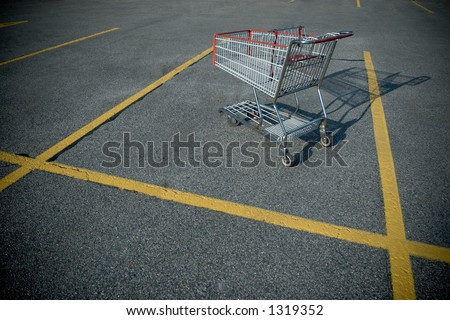 Shopping cart on a deserted parking lot - stock photo