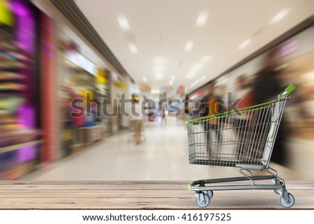 Shopping cart on Wood floor with People  shopping in the supermarket, motion blur - stock photo