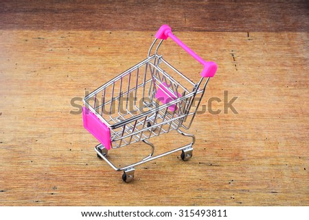 Shopping cart or trolley on wooden background - stock photo