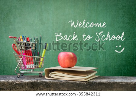 Shopping cart, school supplies, stationery, notebook, apple on dark wood top and grunge green chalkboard background w/ text message welcome back to school & smiley emotiicon for starting new semester - stock photo